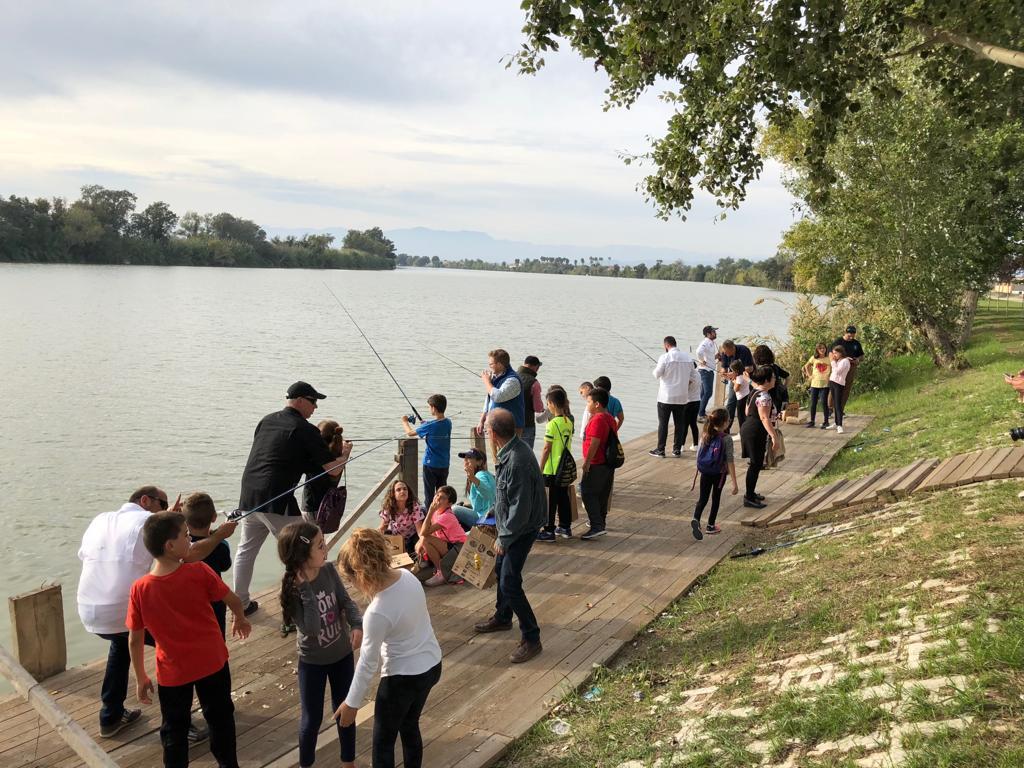 Los niños y niñas a orillas del Ebro, muchos de ellos con una caña en sus manos por primera vez
